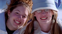 Close-up faces of two laughing girls in winter outdoor wear - stock footage