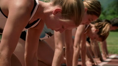 Close-up of women runners lined up at starting blocks and taking off to race - stock footage