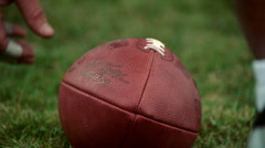 Close-up hand tilting a football on grass Stock Footage