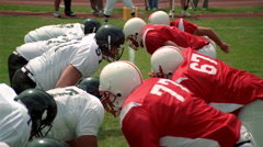 Opposing football players crashing into each other and falling down Stock Footage