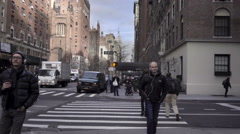 Man with earbuds walking on Lower 5th Ave Empire State Building Manhattan NYC Stock Footage