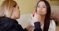 Smiling woman getting makeup applied Stock Footage