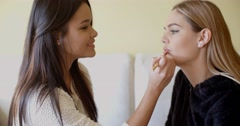 Woman Putting Make up to her Pretty Friend Stock Footage
