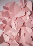 Delicate romantic background of pink paper hearts - stock photo