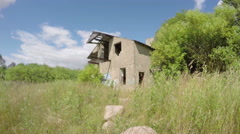Old desolate building in the green meadow on breezy sunny day, time lapse 4 k Stock Footage