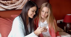 Female friends texting together Stock Footage