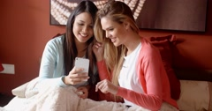 Friends on bed looking at phone Stock Footage