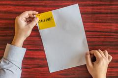 Hands holding blank page with yellow note attached by heart shaped paper clip Stock Photos