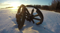 Two antique wooden wheels in the snow during sunset, time lapse 4K Stock Footage