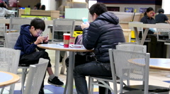 Father and son playing mobile game in modern mall food court cafeteria Stock Footage