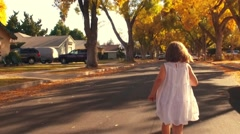 Happy girl child white dress running away POV autumn city street Slow motion Stock Footage