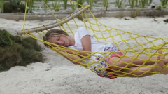 Young girl relaxing in a hammock on the sea beach Stock Footage