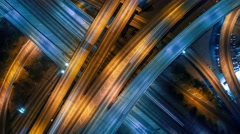 Vertical aerial view panning up over traffic on freeway interchange at night 4K - stock footage