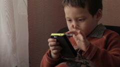 Ittle boy playing a game on your phone Stock Footage