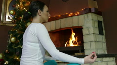Sexy Woman in blue pants  Practicing Yoga In Front Of Fire Place At Home 4K 2 Stock Footage