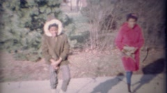 1971: African sisters find puppy in long winter warm coats. Stock Footage
