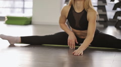 A woman athlete doing stretching. while in the splits she stretches forward. in Stock Footage