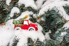 Christmas holiday celebration concept with snow and Christmas tree on toy car Stock Photos