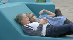 Two girls lying on back on a blue bench in Museumsquartier, Vienna Stock Footage