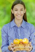 smiling teenage girl with basket of apples - stock photo