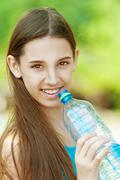 Young dark-haired girl drinking water Stock Photos