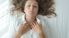 Top View of Young Woman Sending Air Kiss Lying on Bed Stock Footage