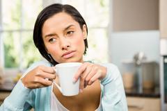 Upset brunette holding white cup - stock photo