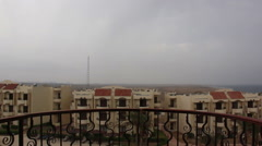 Man on the balcony with sea view on the phone is a storm and lightning in Egypt Stock Footage