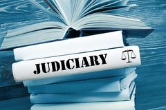 Book with Judiciary word on table in a courtroom or enforcement office. Toned - stock photo