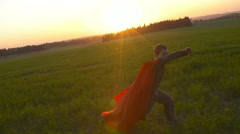 Young boy with a Superman cape outdoors in a field during sunset Stock Footage