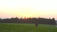 Boy with a Superman cape running in a field during sunset Stock Footage