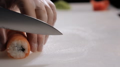 Cooking sushi rolls in the studio. cutting into portions, a round roll of rice Stock Footage
