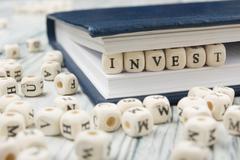 Invest word written on wood block. Wooden ABC - stock photo