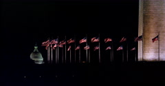 Flags at the base of the Washington Monument at night, dome of US Capitol Stock Footage