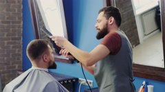 Male barber at work, doing hairstyle young man Stock Footage