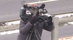 Television news cameraman filming at emergency accident scene on highway - stock footage