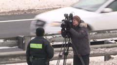 Television news cameraman filming at emergency accident scene on highway Stock Footage