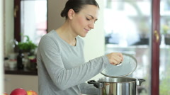 Young woman smelling the nice aromas from her meal in a pot HD Stock Footage