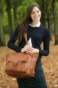 Beautiful young woman walking outdoors with bag on an autumn day - stock photo