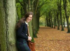 Young woman smiling and relaxing outdoors on an autumn day - stock photo