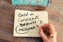 Handwritten text BUILD A CONSISTENT BRAND MESSAGE - stock photo