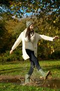 Young woman walking in the park and kicking a puddle of water Stock Photos