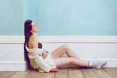 Smiling woman sitting on floor alone with underwear and sweater Stock Photos