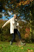 Carefree woman walking in the park and kicking a puddle of water - stock photo