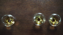 Glasses of whiskey on wooden table with copy space Stock Footage
