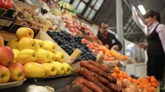 Woman buys vegetables at a farm market. Showcase with lots of vegetables and - stock footage