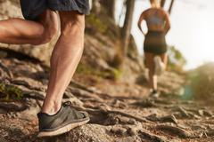 Athletes run through rocky terrain Stock Photos