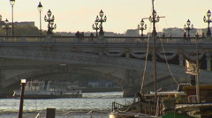 Bridge over river Seine in Paris with people walking and boat crossing Stock Footage