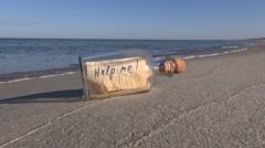 "Phrase ""Help me!"" written on the paper in the bottle on the beach Stock Footage"