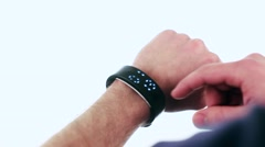 A Man Adjusts a Fitness Bracelet on His Arm. Stock Footage